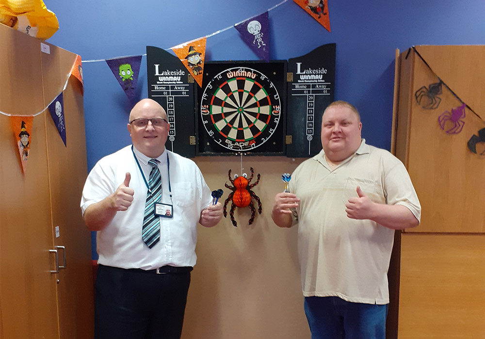 residents playing darts with staff