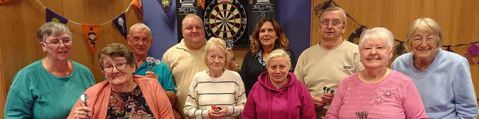10 residents in front of a dart board