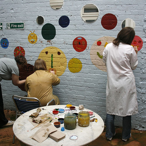 artists painting on a wall
