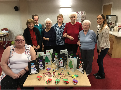 A group showing the items they made during the Christmas crafts course